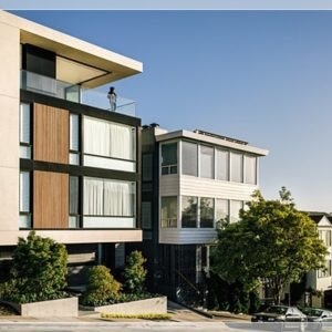 This is the front of the house showcasing the glass walls on two levels and a large balcony with glass railings at the top floor. Image courtesy of Toptenrealestatedeals.com.