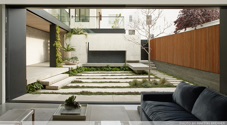 The patio at the lowest level of the house has a large open wall that leads to the backyard garden with concrete slab walkways and a built-in concrete bench on the side. Image courtesy of Toptenrealestatedeals.com.