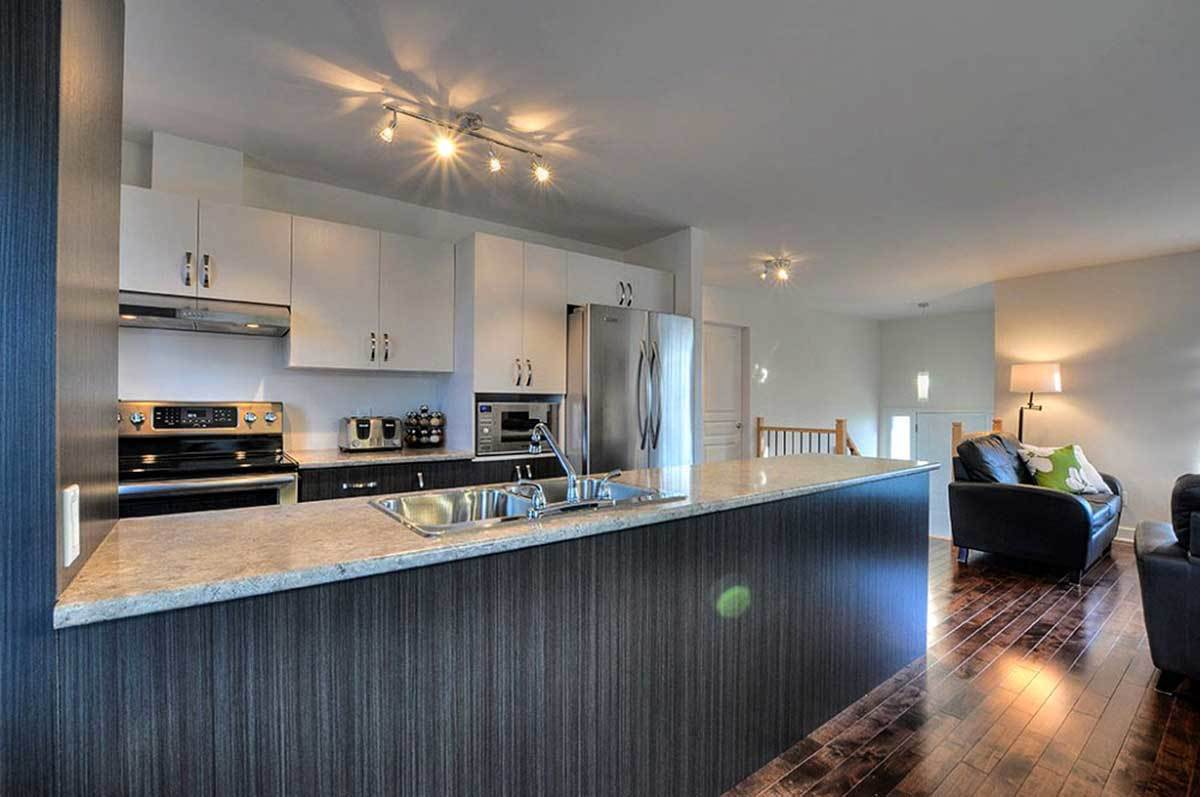 The kitchen is equipped with sleek cabinetry, stainless steel appliances, and a granite top peninsula fitted with an undermount sink.