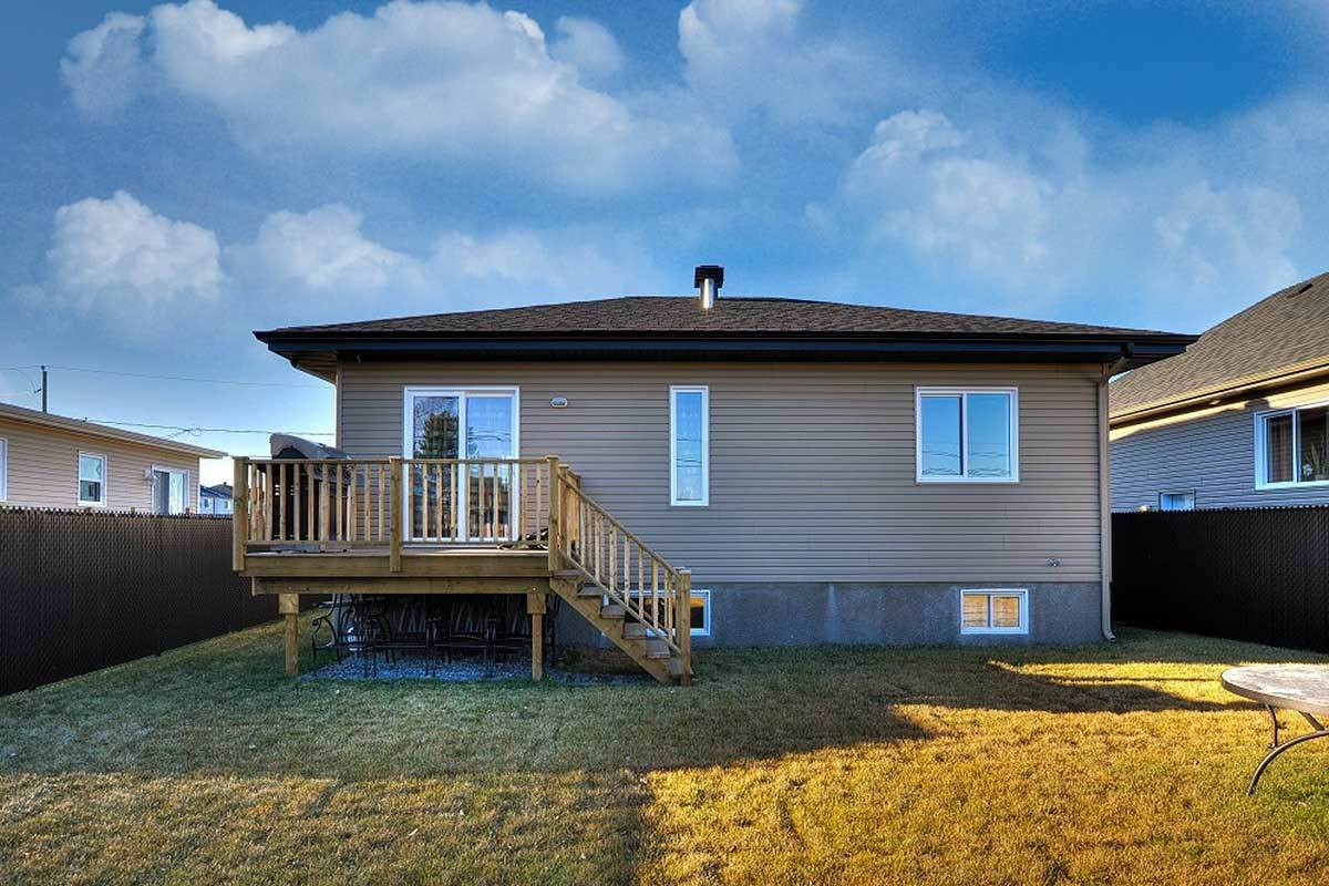 Rear view with taupe horizontal siding, glazed windows, and a wooden staircase that leads to the covered deck.