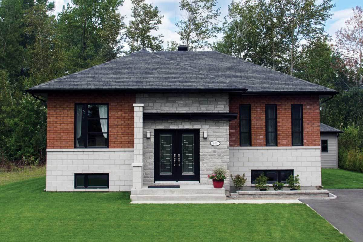Home facade showcasing the brick exterior, hipped roofs, stone accents, and a french entry door.