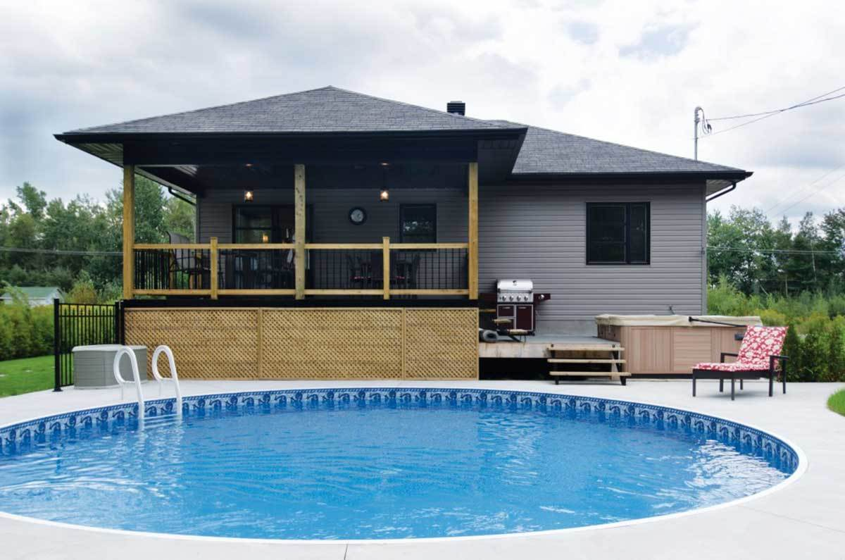Another version of rear exterior showcasing a covered porch, deck with summer kitchen, and a round swimming pool.