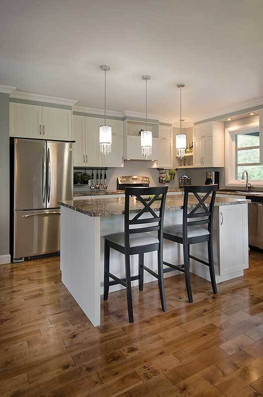 The kitchen is equipped with white cabinetry, granite countertops, stainless steel appliances, and an island bar well-lit by glass pendants.