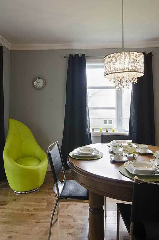 The dining area offers a drum pendant light, round dining set, and a bright green chair that stands out against the gray walls.