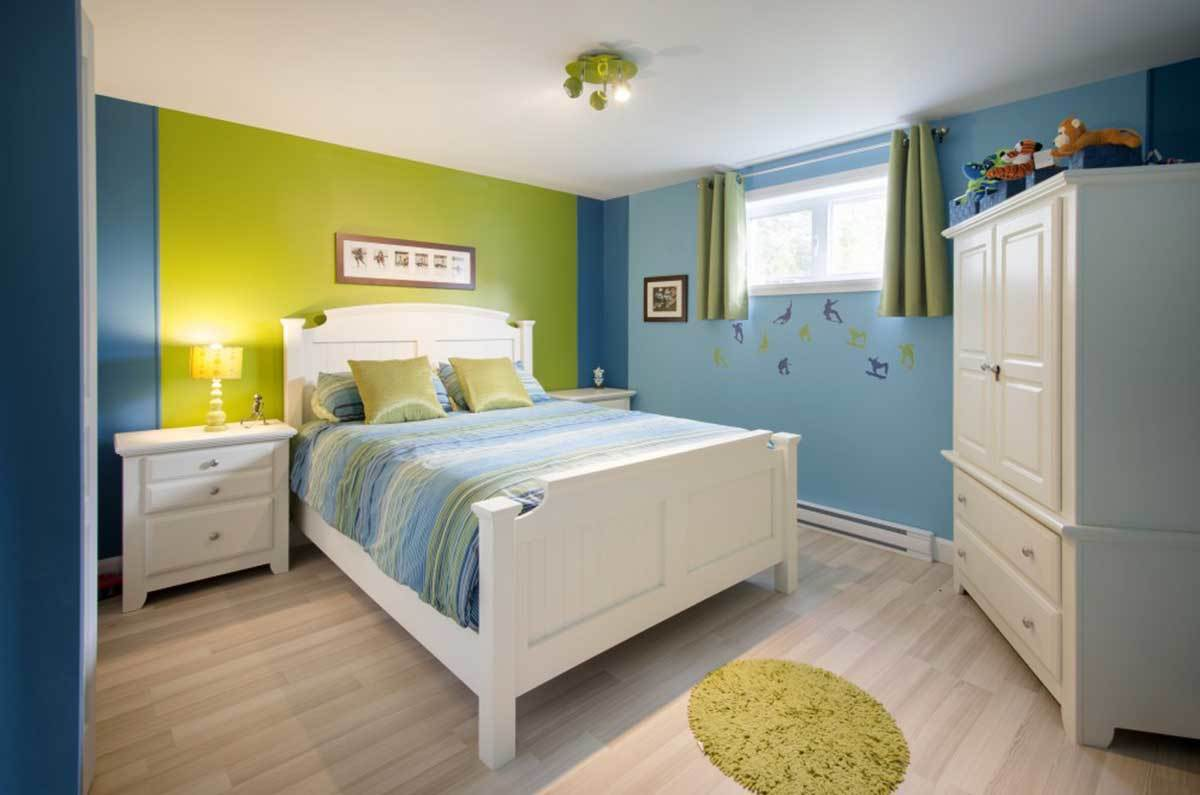 Kid's bedroom with multi-colored walls, white furnishings, and light hardwood flooring topped by a round shaggy rug.