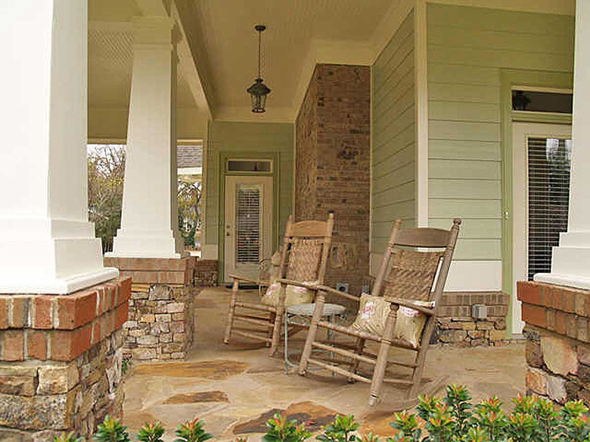 A closer look at the porch shows the round side table and wooden rocking chairs accented with floral pillows.