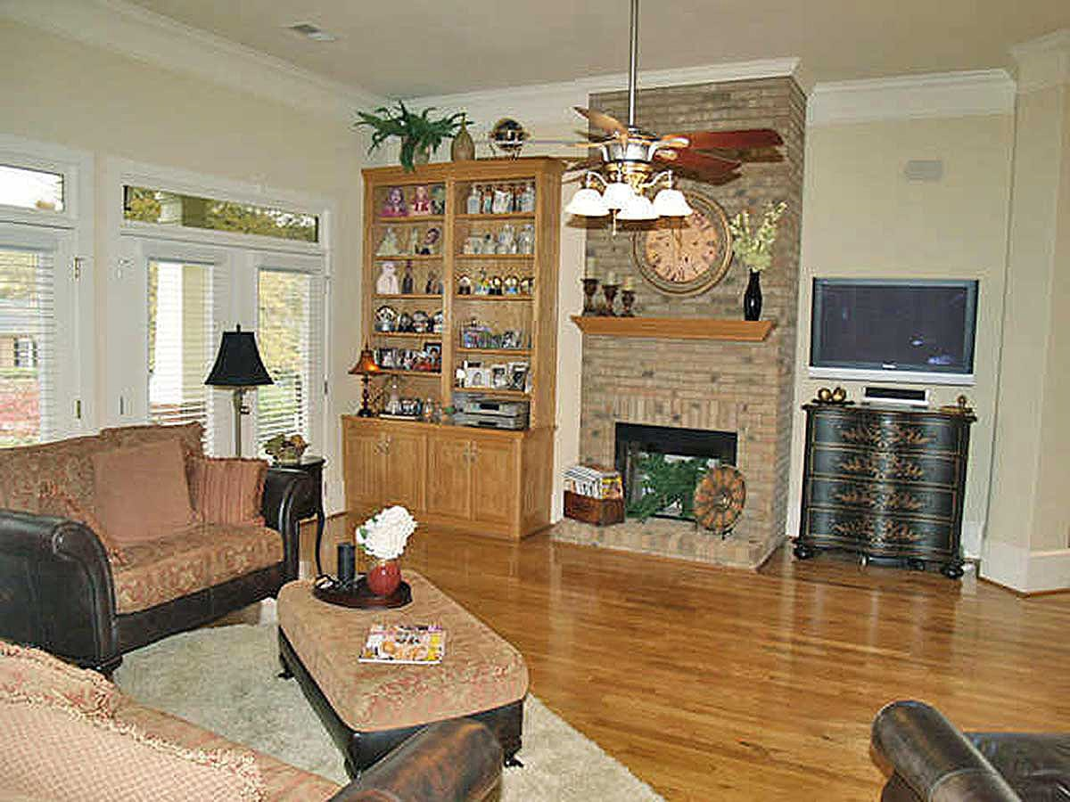 The living room offers cushioned seats, a matching ottoman, and a stone fireplace flanked by wooden cabinets.
