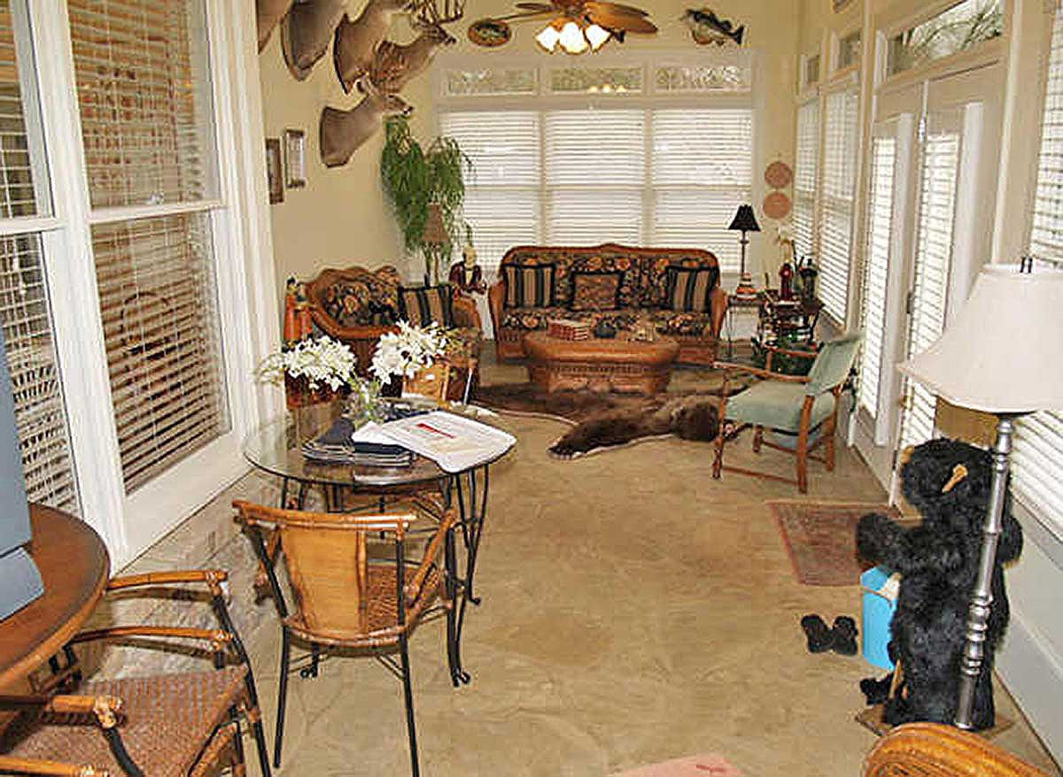 Covered porch filled with cozy seats, wooden and glass top tables, antler decors, and a cowhide rug that lays on the flagstone flooring.