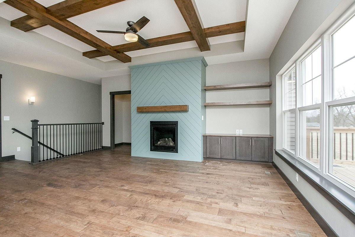 The living room has a chevron fireplace sitting next to the built-in shelves and cabinets along with a step ceiling adorned with exposed wood beams.