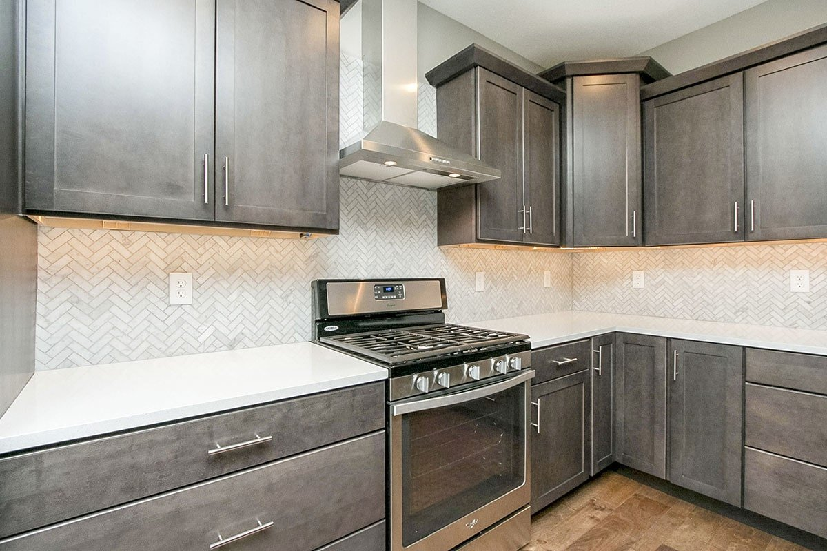 The kitchen is equipped with stainless steel appliances and natural wood cabinetry fixed against the herringbone tile backsplash.