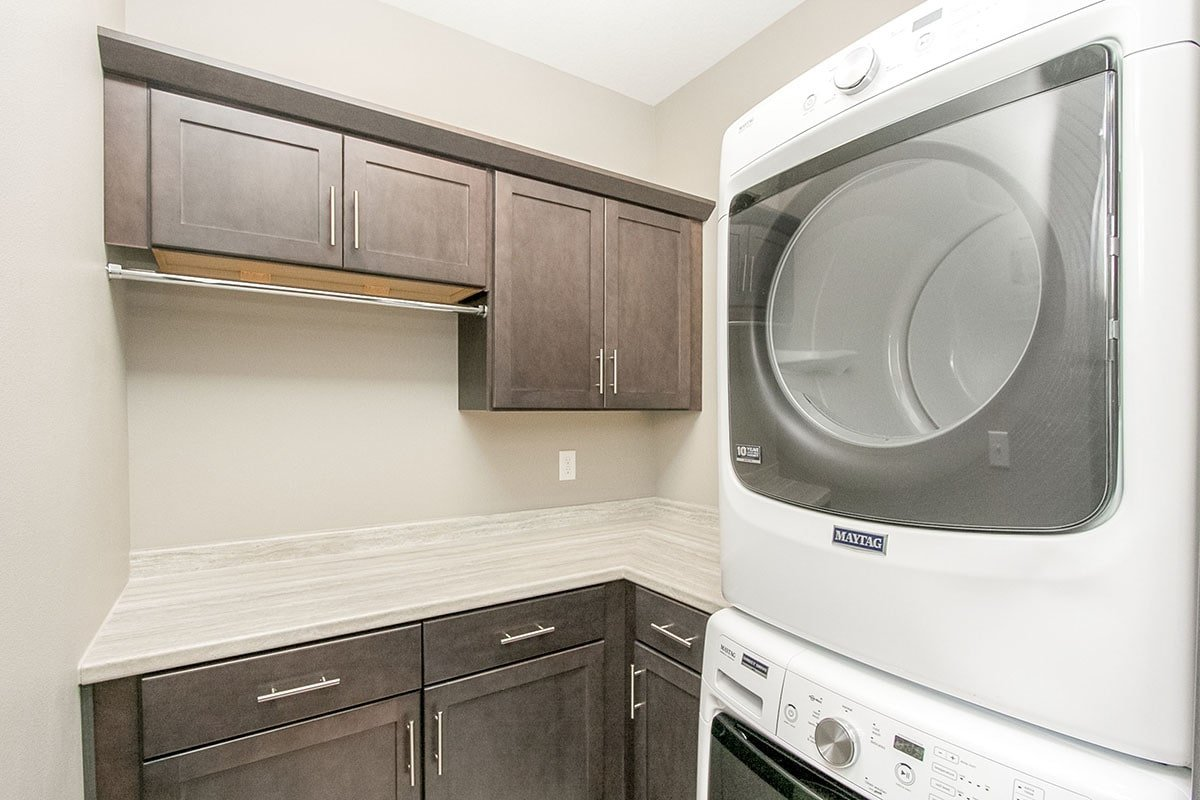 The utility room offers white front-load appliances, granite countertops, and wooden cabinets.