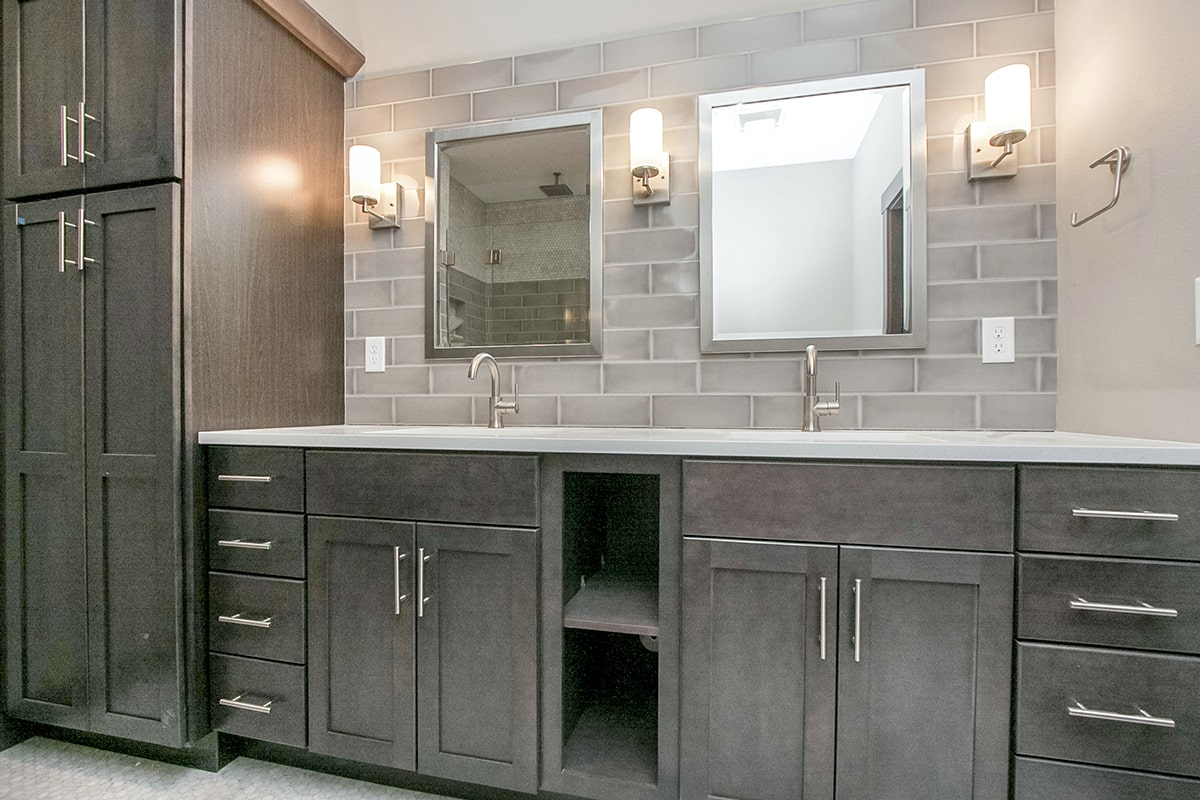 Bathroom with chrome framed mirrors and a dual sink vanity matching with the floor to ceiling cabinet.