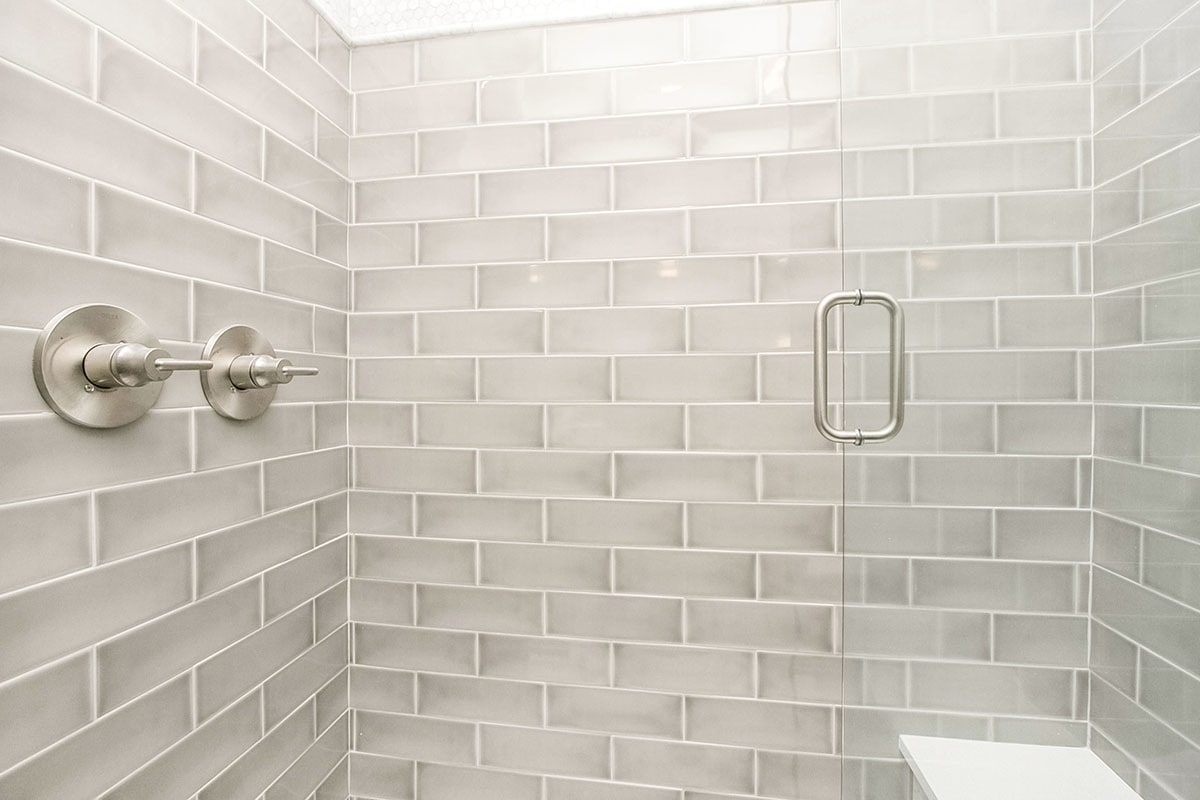 The walk-in shower is clad in light gray subway tiles mounted with chrome fixtures.
