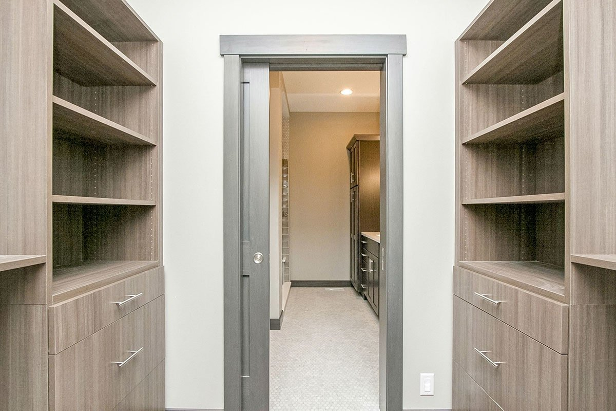 A gray pocket door opens to the walk-in closet filled with natural wood drawers and shelves.
