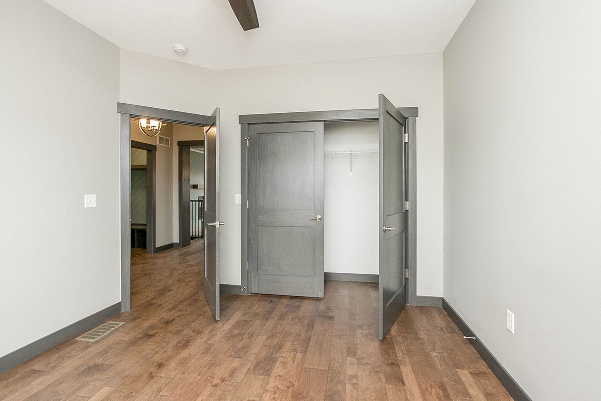 The opposite view shows the linear closet enclosed in a gray double door.
