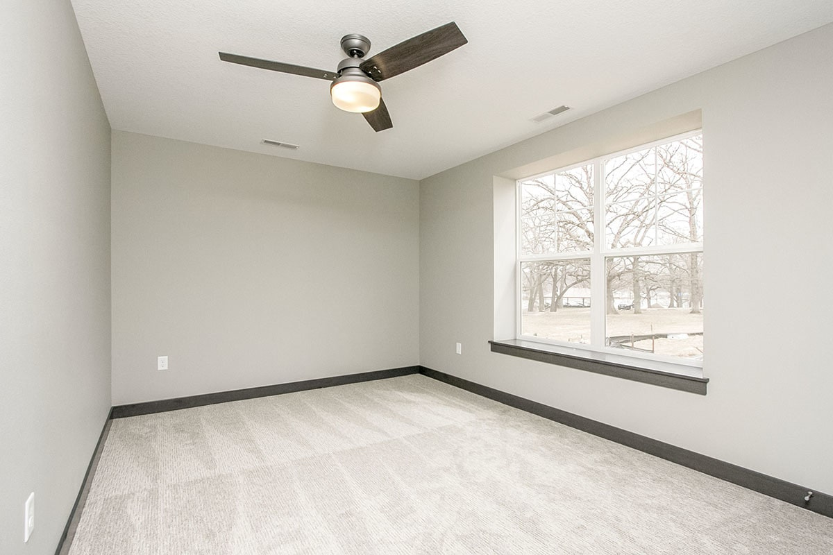 Another bedroom with gray carpet flooring and a regular white ceiling mounted with a sleek fan.