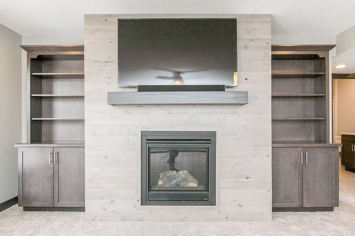 A closer look at the glass-enclosed fireplace topped with a dark wood mantel and a flat-screen TV.