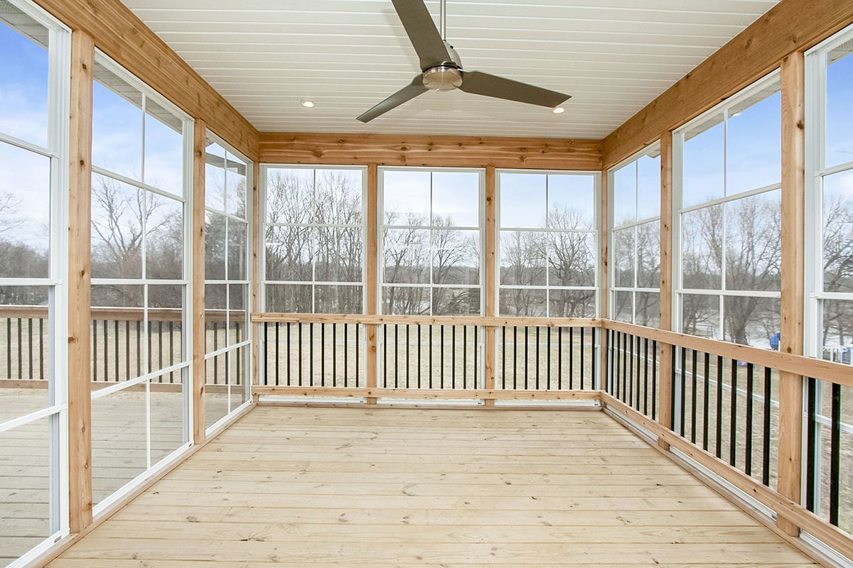 Slim wooden columns and white trims frame the screened porch that's crowned with a white shiplap ceiling.