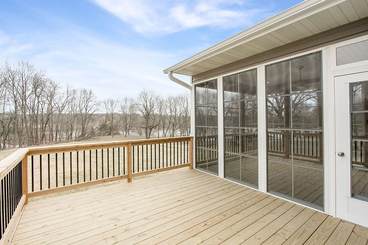 Off the screened porch is a roomy deck with wide plank flooring and wrought iron railings.