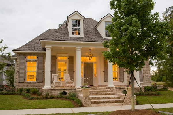 Home's front view showcasing hipped roofs, dormer windows, wooden shutters, and a front porch supported by exterior columns.