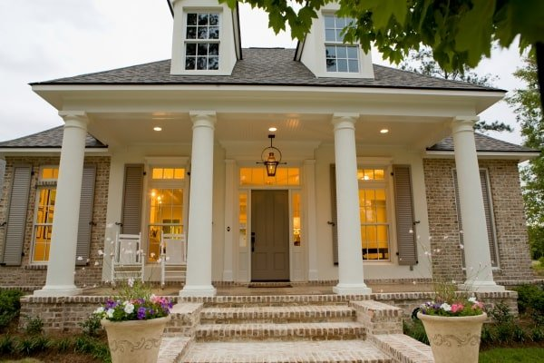A closer look at the front porch shows the white rocking chair and a wooden front door lit by a glass pendant light.