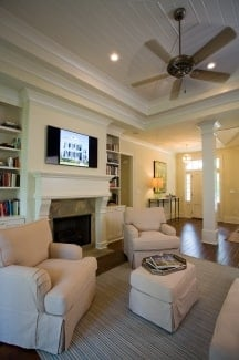 Two skirted armchairs along with a matching ottoman sit in front of the fireplace.
