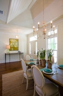 Formal dining room with round back chairs, a wooden dining table, and a buffet bar adorned with a bold artwork.