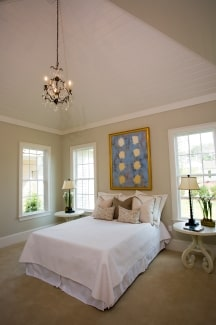 A beaded chandelier illuminates the primary bedroom furnished with a white comfy bed and round nightstands.