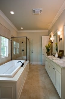 Primary bathroom with a walk-in shower, white vanity, and a deep soaking tub fitted with wrought iron fixtures.