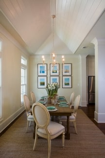 A warm candle chandelier hanging from the cathedral ceiling brightens the dining room.