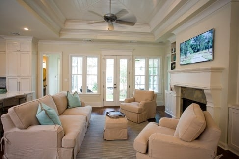 The living room has cozy beige seats, a step ceiling, and a fireplace topped with a landscape painting.