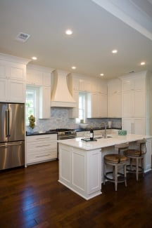 A pair of round cushioned stools complement the marble top breakfast island.