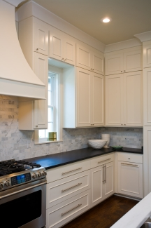 The kitchen is equipped with white cabinetry, absolute black granite countertop, and stainless steel appliances.