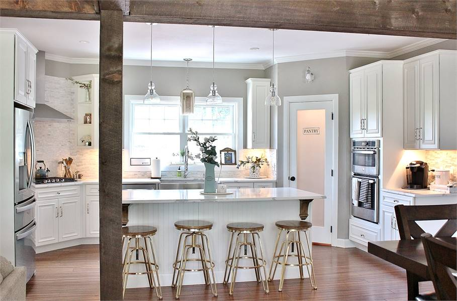 Rustic wood beams define the kitchen with white cabinetry stainless steel appliances, and a breakfast island bar.