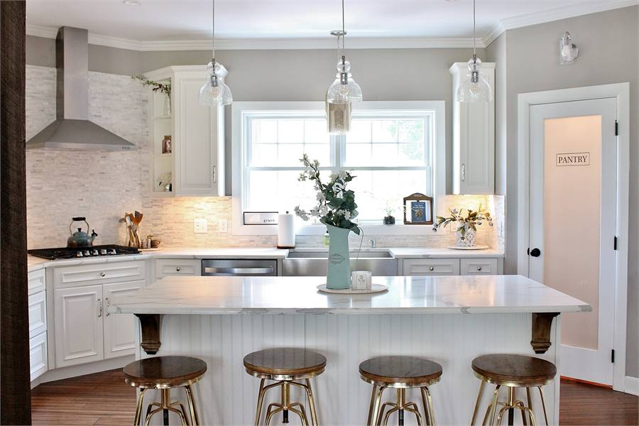 Glass dome pendants illuminate the white beadboard island that's paired with round bar stools.