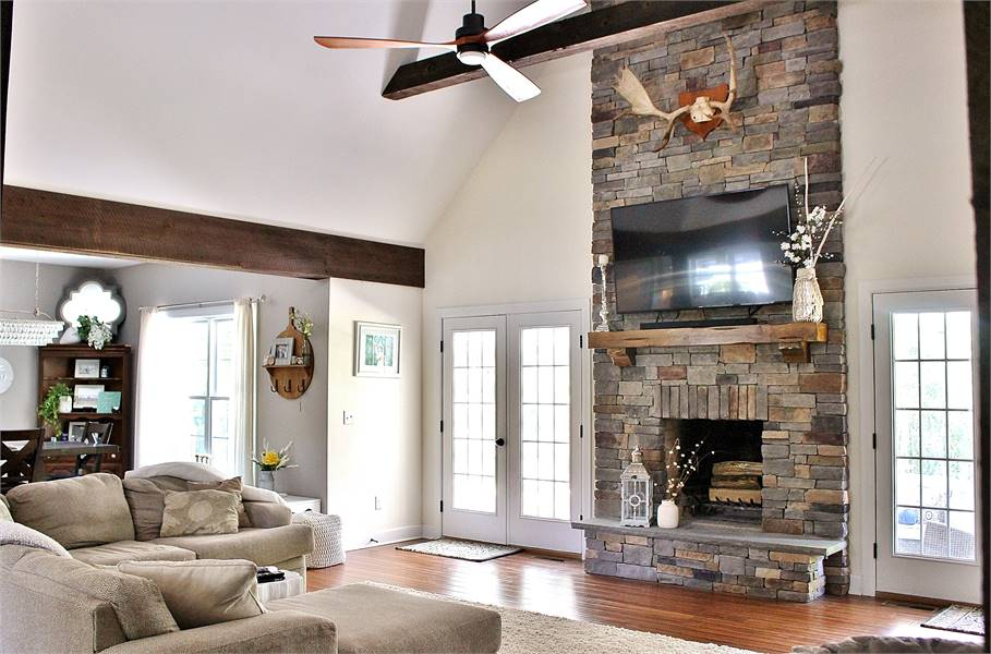 The living room offers beige seats, ceiling fan, and a stone fireplace with a wall-mounted TV on top.