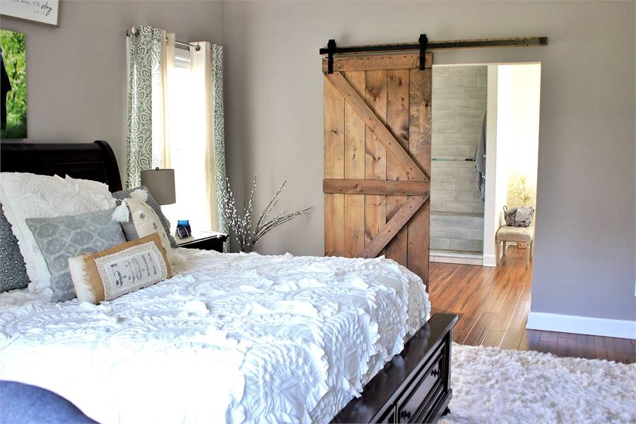 Primary bedroom with wide-plank flooring and a barn door that leads to the primary bath.