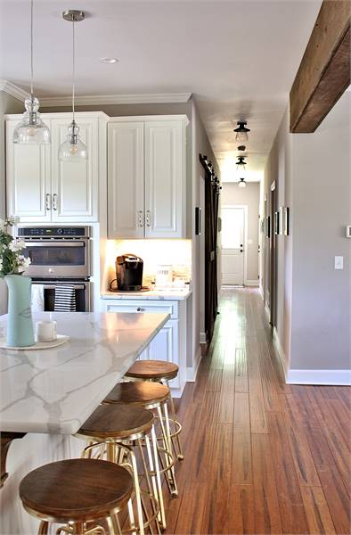 A hallway situated next to the kitchen leading to the bedrooms, utility, and future spaces.