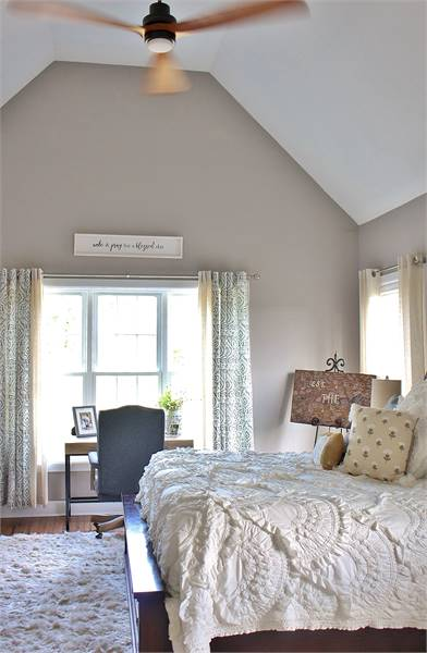 This bedroom is furnished with a cozy wooden bed and a sleek desk paired with a blue swivel chair.