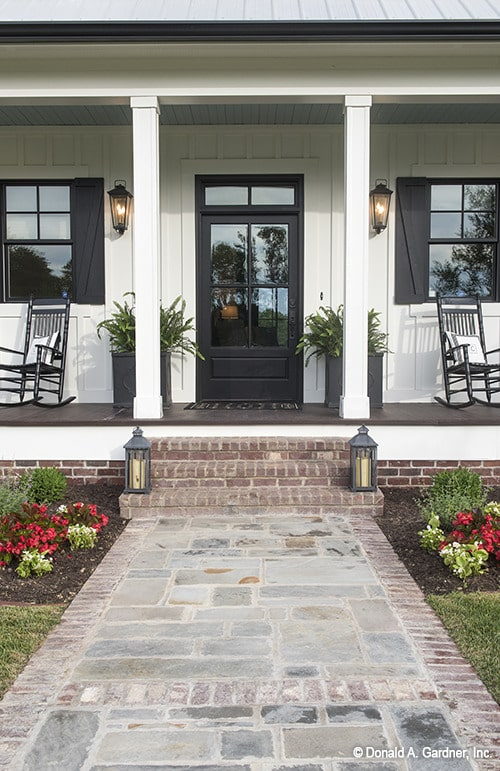 A brick pathway leads to the home entry with a glazed dark wood front door flanked by glass sconces and fresh potted plants.