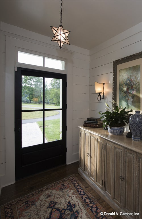 The foyer has a natural wood console table and a classic area rug lit by a star pendant light.