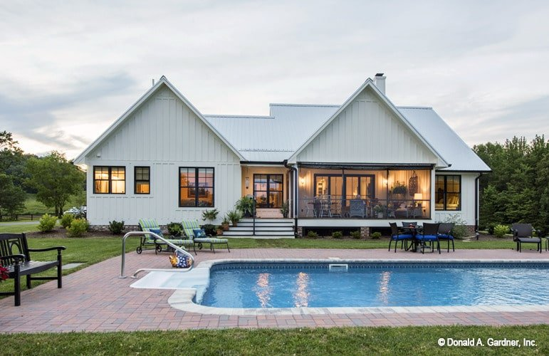 Home's rear view showcasing a screened porch and a backyard pool.