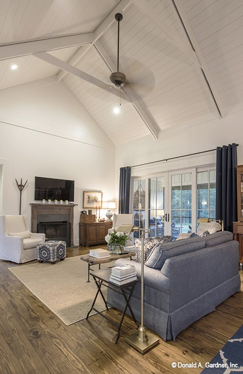 The living room has a cathedral ceiling with exposed beams and a french door that leads out to the screened porch.
