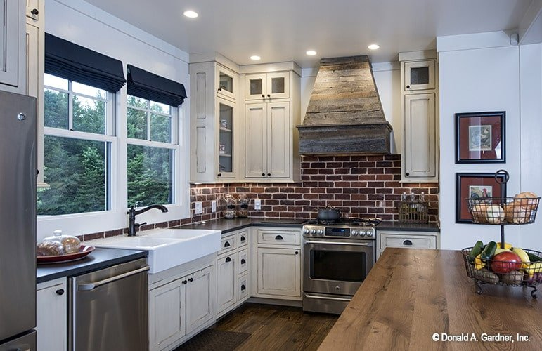 The kitchen is equipped with a farmhouse sink, white cabinets, stainless steel appliances, and an island bar topped with a two-tier food stand.
