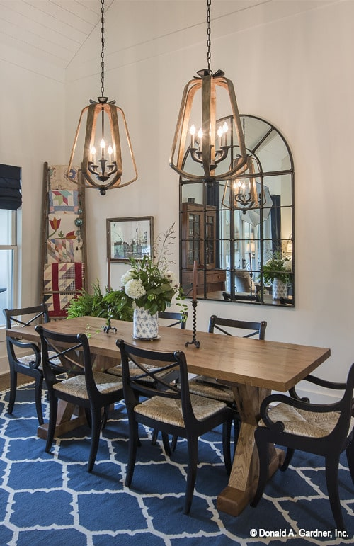 Large candle pendants hanging from the vaulted ceiling illuminate the dining room offering a rectangular dining set.