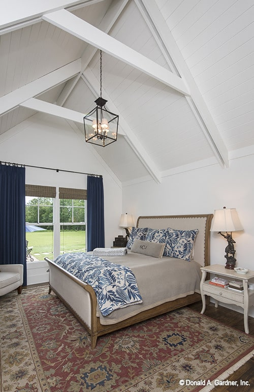 The primary bedroom showcases a cozy wooden bed over a vintage area rug along with white framed windows covered in wicker shades and deep blue draperies.