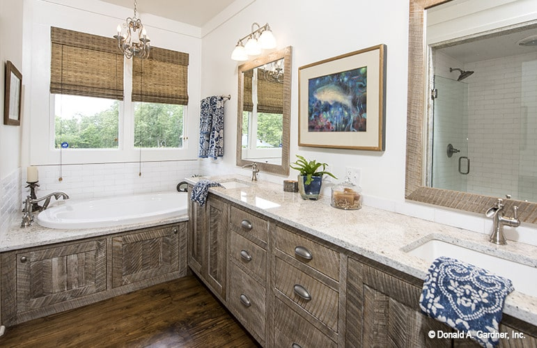 Primary bathroom with a drop-in tub and a dual sink vanity topped with chrome fixtures and a granite countertop.