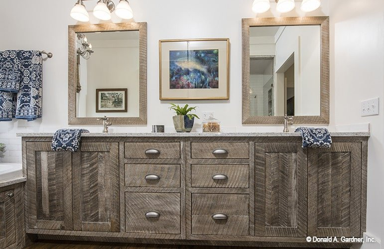 A closeup look at the wooden vanity with herringbone cabinets and pull-out drawers under the framed mirrors and gorgeous artwork.