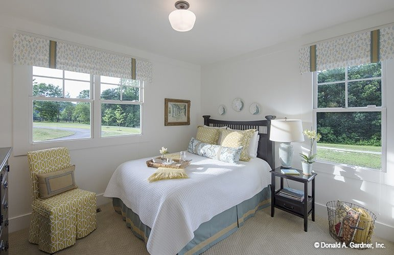 Another bedroom with a bright and airy ambiance brought by the white walls and framed windows.