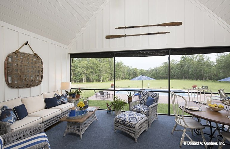 Screened porch with blue carpet flooring, a high cathedral ceiling, and white shiplap walls adorned with decorative wooden paddles.